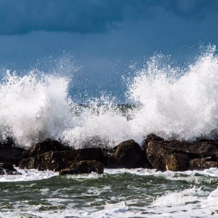 the waves are crashing (against the rocks)